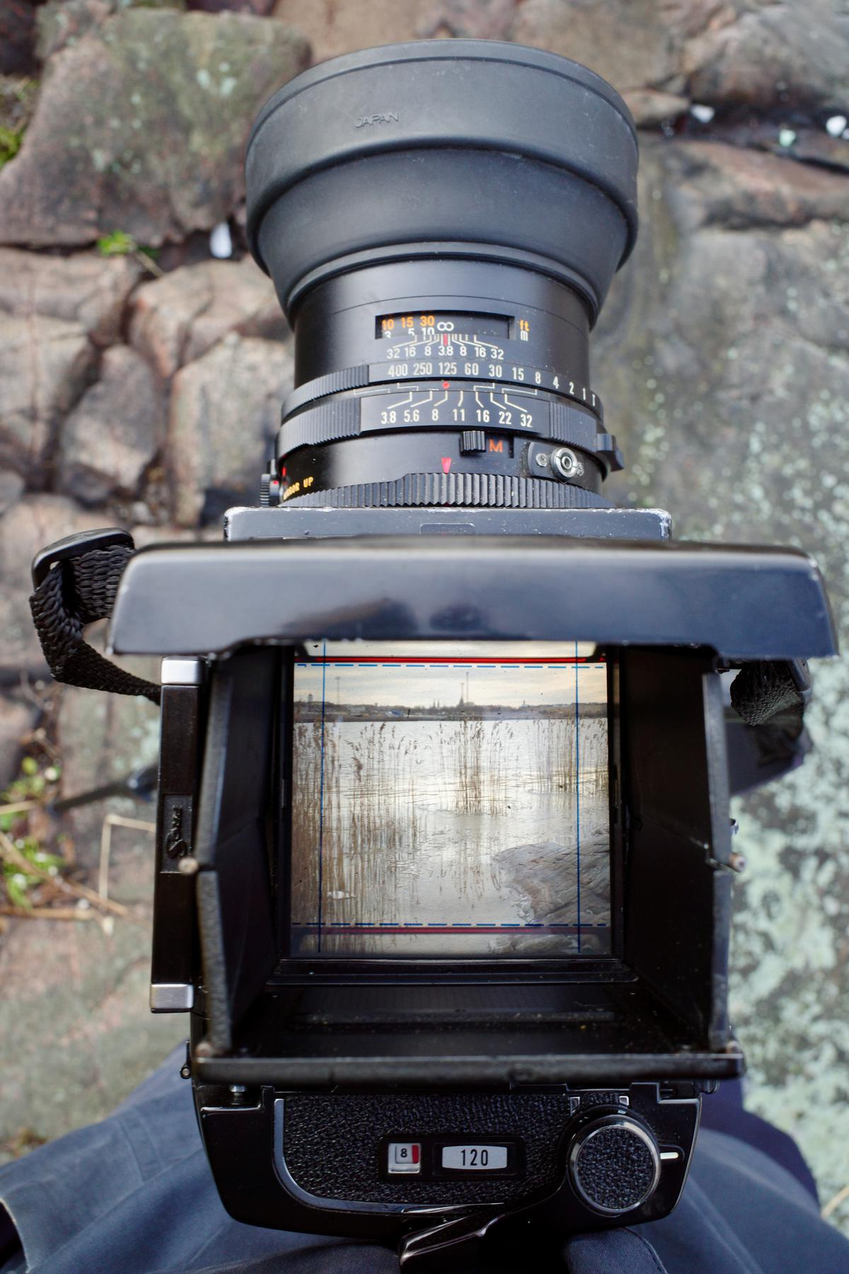 The medium-format camera seen from the above. The viewfinder shows a landscape with rocky seashore and reeds in the front and a city in the background.