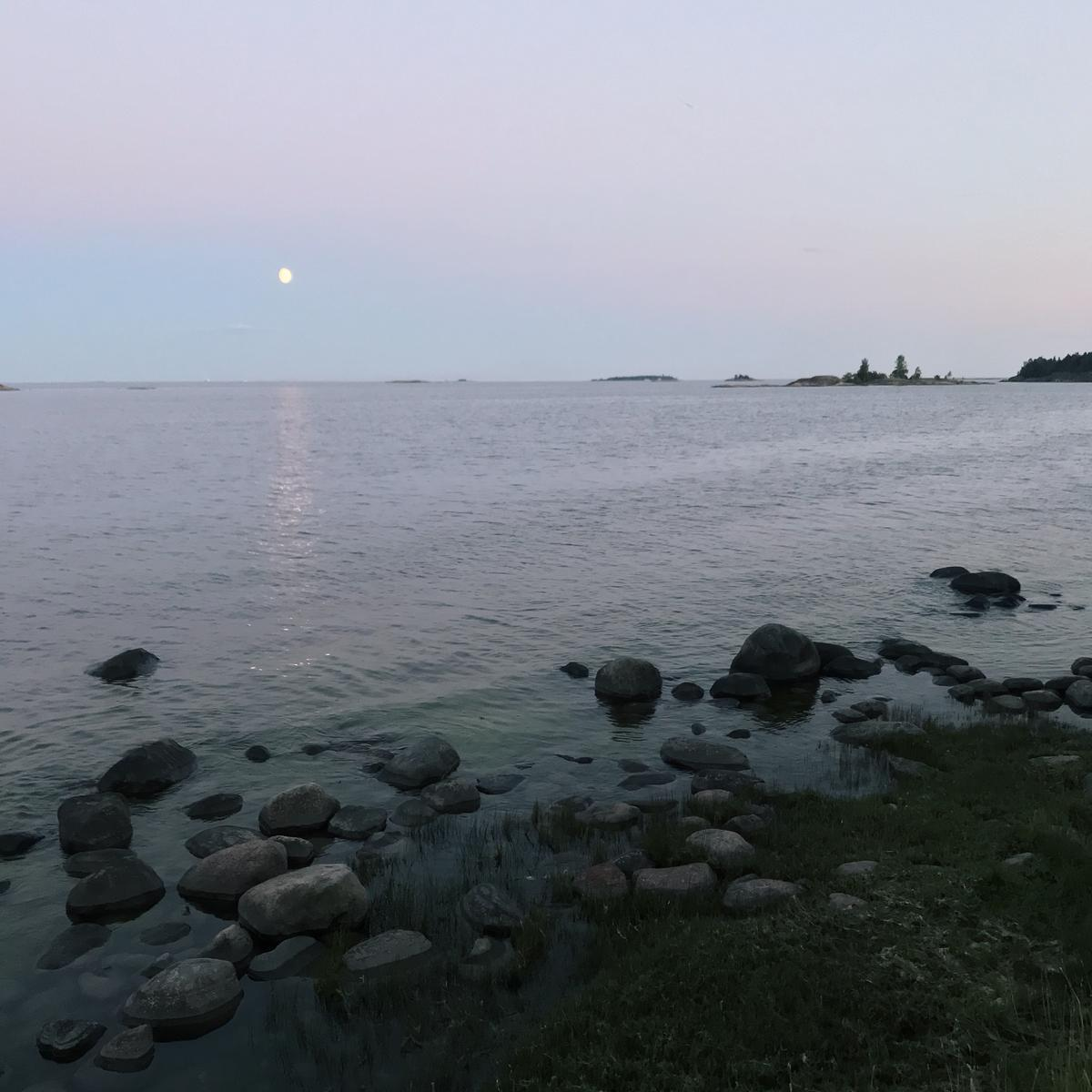 Moon shining over the sea in the evening. There's a rocky shore close to the camera and small islands in the horizon.
