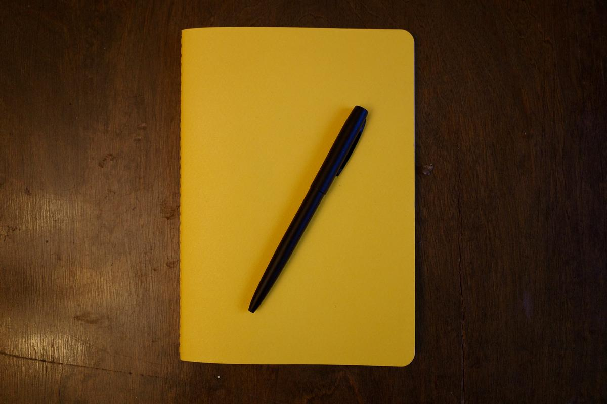 A yellow notebook laying on a table with a black ballpoint pen on top of it.