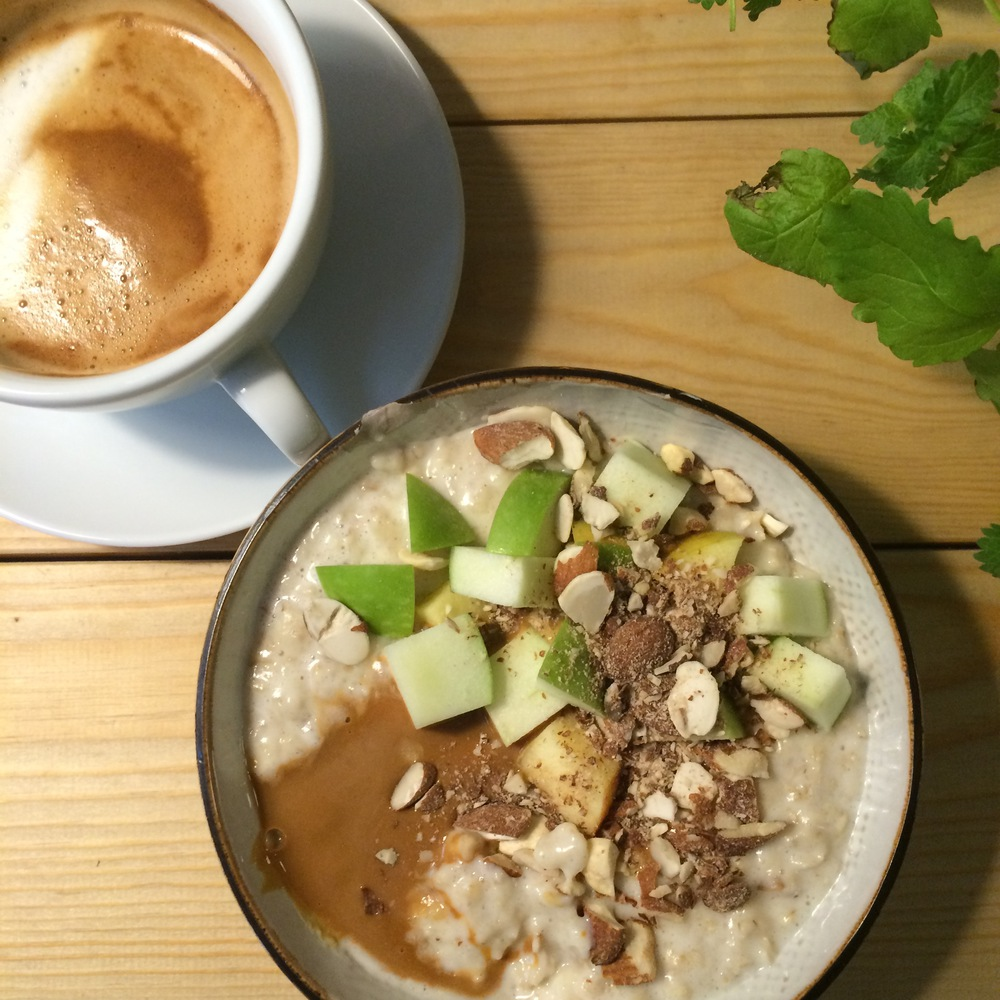 A bowl of oat porridge with fresh apple and caramel sauce. Yum.